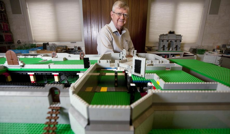 In this March 25, 2015 photo, retired dermatologist Dr. Robert Carney Jr., of Decatur, Ill., sits behind the early stages of a LEGO replica of Caernarfon Castle. The Welsh government commissioned Carney to build the castle after seeing his work on other LEGO castles. (Danny Damiani/Herald & Review via AP)