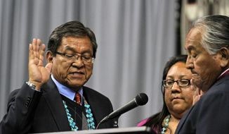 Russell Begaye, left, is sworn in as president of the Navajo Nation by Navajo Nation Supreme Court Chief Justice Herb Yazzie at Fighting Scouts Events Center in Fort Defiance, Ariz., Tuesday, May 12, 2015. (Alexa Rogals/The Daily Times via AP)