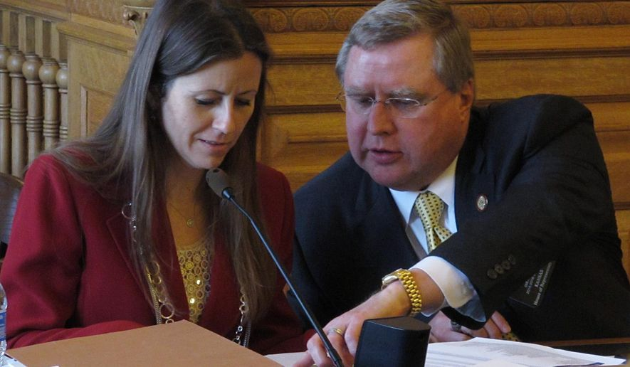 Kansas state Reps. Kasha Kelley, left, an Arkansas City Republican, and Mark Hutton, right, a Wichita Republican, confer over a tax proposal during a House committee meeting, Tuesday, May 12, 2015, at the Statehouse in Topeka, Kan. Hutton supports efforts to roll back an income tax break granted in 2012 to business owners and farmers, while Kelley opposes them. (AP Photo/John Hanna)