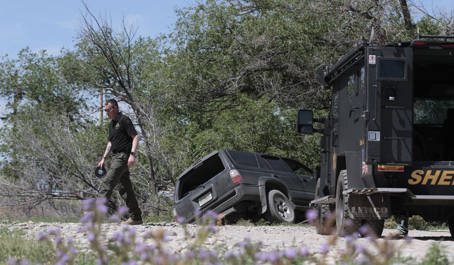A San Juan County Sheriff's Office deputy investigates, Monday, May 11, 2015, the scene of a fatal shooting off Bluff Road in Shiprock, N.M. Authorities say police shot and killed two people in Shiprock in connection with a chase that began in Cortez, Colo. (Jon Austria/The Daily Times via AP)