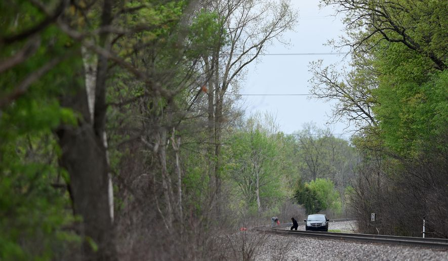 Authorities inspect the train tracks following a fatal train crash on Monday with a pedestrian on Tuesday, May 12, 2015 in Lima Township, Mich. State police Sgt. Mark Thompson says that authorities were called to the train tracks in Lima Township around 11:30 p.m. Monday. Joyce Williams of Huron Valley Ambulance says the person was pronounced dead at the scene. (Melanie Maxwell/The Ann Arbor News via AP) LOCAL TELEVISION OUT; LOCAL INTERNET OUT