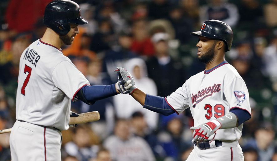 Minnesota Twins' Danny Santana (39) celebrates with Joe Mauer (7) after scoring on a Torii Hunter sacrifice fly against the Detroit Tigers in the eighth inning of a baseball game in Detroit Tuesday, May 12, 2015. (AP Photo/Paul Sancya)