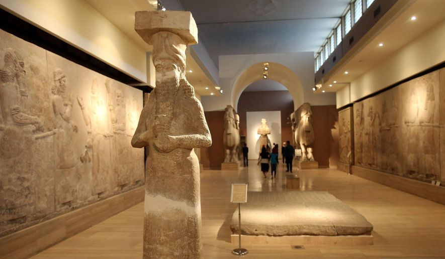 People observe ancient artifacts at the Iraqi National Museum after its reopening in the wake of the recent destruction of Assyrian archaeological sites by the Islamic State group in Mosul, as they visit the museum in Baghdad in this Sunday, March 15, 2015, file photo. (AP Photo/Karim Kadim, File)