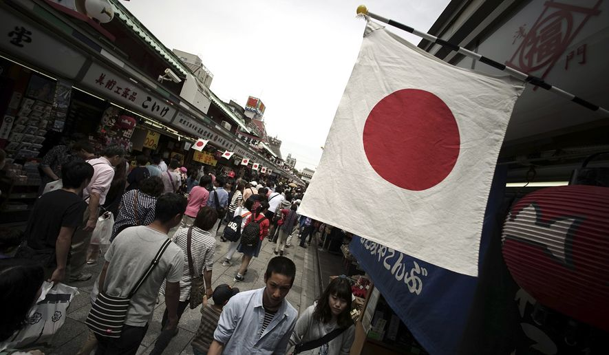 Japanese flags are hoisted as tourists walk though the Nakamise shopping street in front of Sensoji Templehe in the Asakusa district in Tokyo Wednesday, May 6, 2015. Asakusa is an old town in the capital that draws many tourists from across the world. (AP Photo/Eugene Hoshiko)