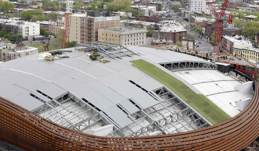 In this May 6, 2015, photo, construction continues on a new roof for the Barclays Center in the Brooklyn borough of New York. A construction project is underway atop the Barclays Center to replace the sprawling over 130,000-square-foot roof with panels of vibrant green grasses and summer flowers. When completed later this spring, it will be one of nation's largest green roofs. (AP Photo/Seth Wenig)