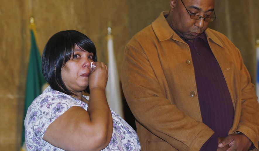 Josephine Baez, left, fights back tears as her husband, Carlos Mason, listens during a news conference to announce additional financial enticements for those who know about gang crimes in the Mile High City, Wednesday, May 13, 2015. The couple lost their 17-year-old son in a gang-related shooting on a northeast Denver street corner in 2007. The Denver Police Department, in partnership with Metro Denver Crime Stoppers, is staging the effort as gang crimes have increased in Denver this year. (AP Photo/David Zalubowski)