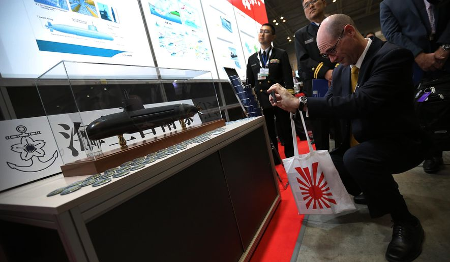 A visitor takes photo of a scale model of a Japanese Maritime Self Defense Force Soryu-class submarine at a first-ever defense industry fair in Yokohama, Wednesday, May 13, 2015. A year after Japan eased a longstanding ban on military exports, barely a trickle of deals has formed for its powerhouse manufacturers who are reckoning with latecomer status in a crowded global industry. (AP Photo/Eugene Hoshiko)