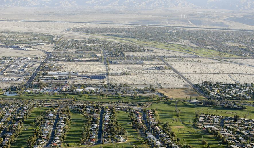 In this April 3, 2015, aerial file photo, lush green golf courses border the edge of the desert in Palm Springs, Calif. (AP Photo/Chris Carlson, File)