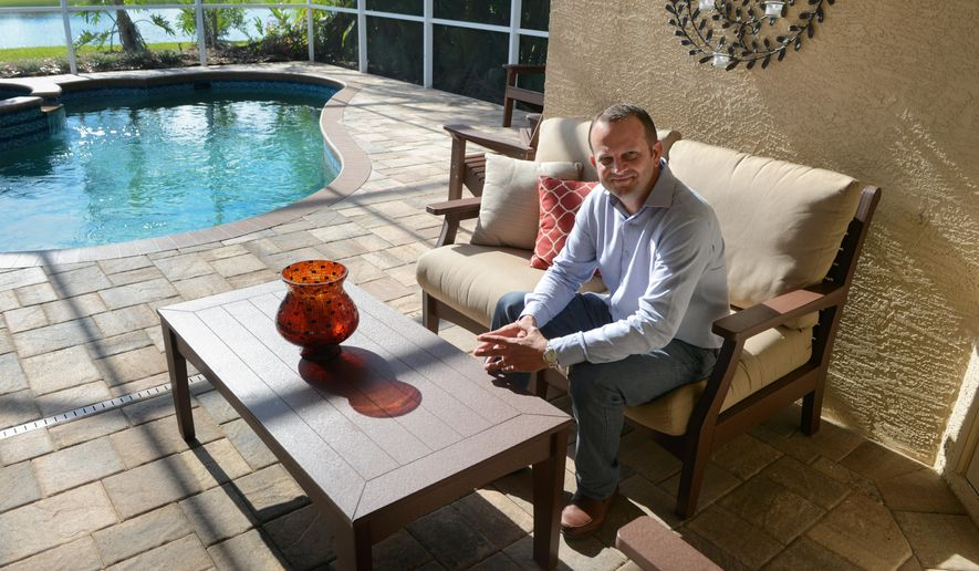 ADVANCE FOR USE SATURDAY, MAY 16, 2015, AND THEREAFTER- In this May 4, 2015 photo, Jim Miller poses for a photo with a Berlin Gardens couch and coffee table at his home in Sarasota, Fla. Jim Miller, a former Mennonite pastor in Sarasota, and his wife have become one of the largest Internet-only marketers of Amish-made furniture. (Dan Wagner/Sarasota Herald-Tribune via AP)  PORT CHARLOTTE OUT; BRADENTON HERALD OUT; TV OUT;  ONLINE OUT