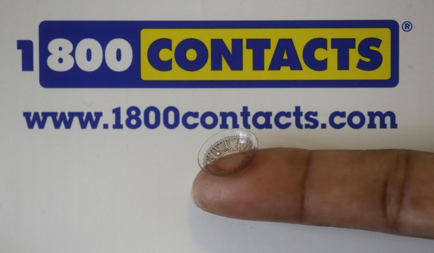 A contact lens is shown in front of a 1-800-Contacts shipping box Wednesday, May 13, 2015, in Salt Lake City. A law banning price-fixing for contact lenses that took effect this week in Utah is a setback for the nation's largest manufacturers that could have ripple effects across the country amid an increasingly bitter fight with discount retailers. (AP Photo/Rick Bowmer)