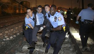 Emergency personnel help a passenger at the scene of a train wreck, Tuesday, May 12, 2015, in Philadelphia. An Amtrak train headed to New York City derailed and crashed in Philadelphia. (AP Photo/Joseph Kaczmarek)