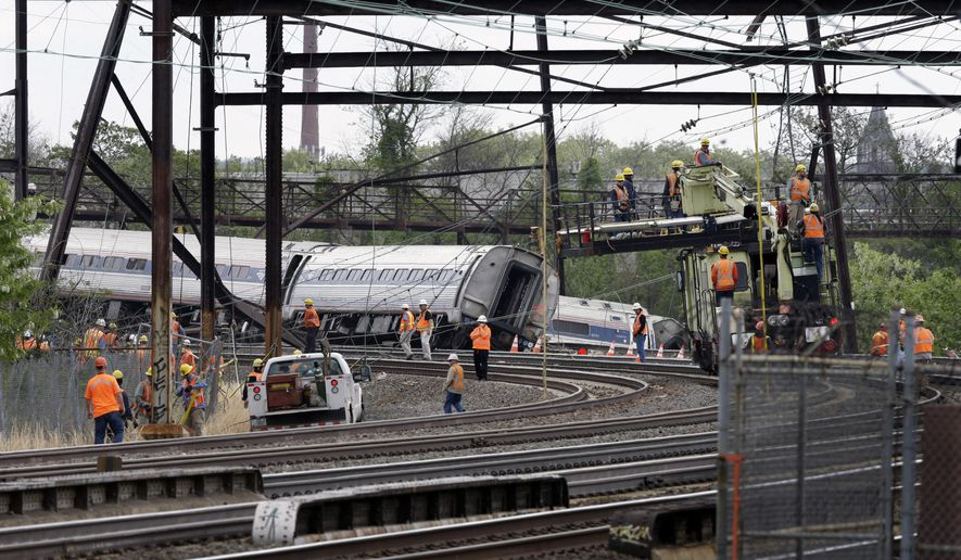 Emergency personnel gather near the scene of a deadly train wreck, Wednesday, May 13, 2015,  after a fatal Amtrak derailment Tuesday night, in the Port Richmond section of Philadelphia. Federal investigators arrived Wednesday to determine why an Amtrak train jumped the tracks in a wreck that killed at least six people, and injured dozens. (AP Photo/Mel Evans)