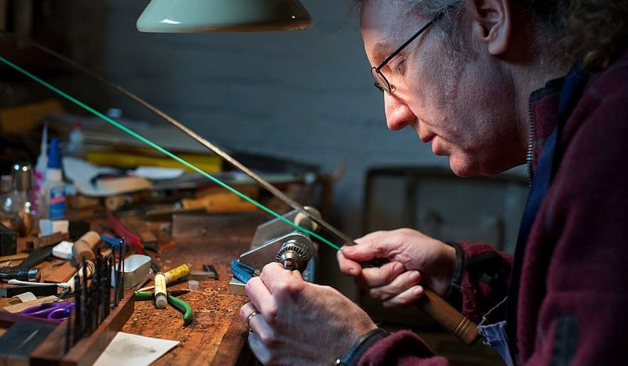 In this photo taken March 26, 2015, violin bow maker Matthew Wehling used a hand-operated drill to modify a bow component called a frog, which is the piece that the musician holds, in his workshop Northfield, Minn. With an ivory import ban, Wehling has replaced ivory bow tips with mastodon for musicians who are worried about international travel. (Jennifer Simonson/Minnesota Public Radio via AP)