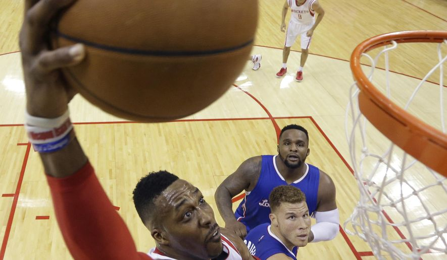 Houston Rockets' Dwight Howard (12) drives to the basket over Los Angeles Clippers' Blake Griffin, center bottom, and DeAndre Jordan, center top, during the first half in Game 5 of the NBA basketball Western Conference semifinals Tuesday, May 12, 2015, in Houston. (AP Photo/David J. Phillip)