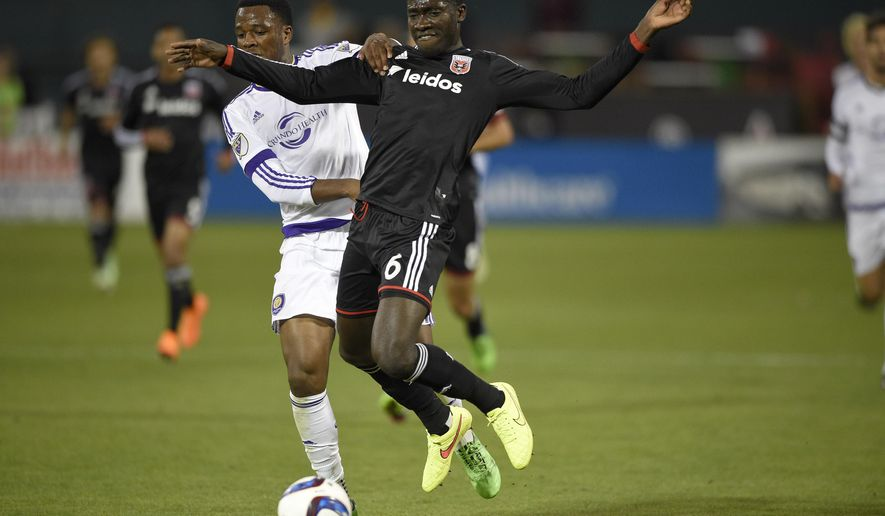 Orlando City forward Cyle Larin, left, battles for the ball against D.C. United defender Kofi Opare (6) during the first half of an MLS soccer game, Wednesday, May 13, 2015, in Washington. (AP Photo/Nick Wass)