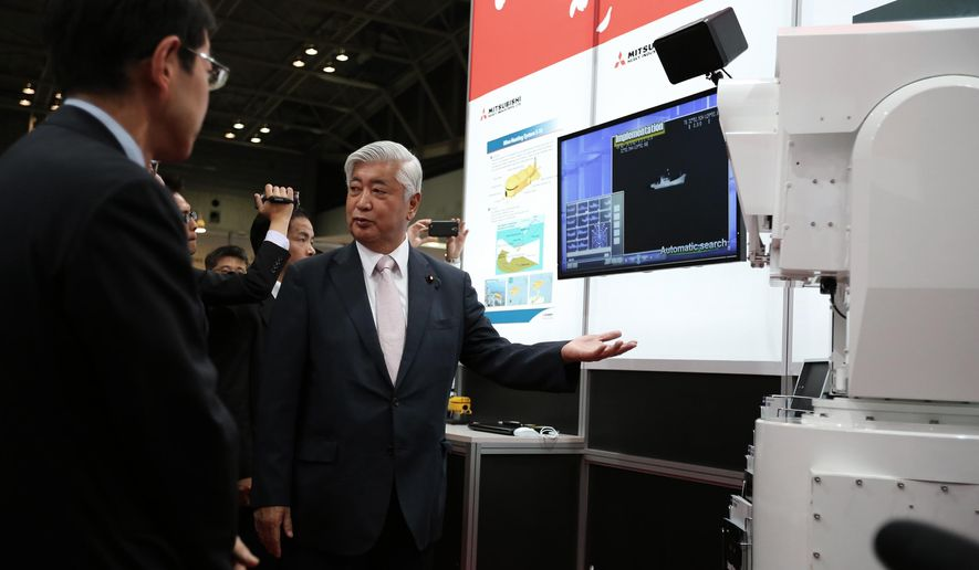 Japanese Defense Minister Gen Nakatani, center, looks at Mitsubishi's laser radar surveillance system at a first-ever defense industry fair in Yokohama, south of Tokyo, Wednesday, May 13, 2015. A year after Japan eased a longstanding ban on military exports, barely a trickle of deals has formed for its powerhouse manufacturers who are reckoning with latecomer status in a crowded global industry. (AP Photo/Eugene Hoshiko)