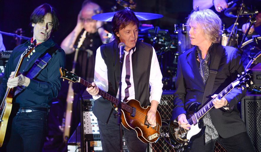 FILE - In this Feb. 14, 2015 file photo, Paul McCartney, center, and his band, including Rusty Anderson, left, and Brian Ray, perform a secret Valentine's Day concert at Irving Plaza in New York. McCartney played a private concert with a crowd that included Wall Street executives and boldface names that included Sting and Oprah. The concert on Tuesday night, May 12, 2015, was part of the Robin Hood Foundation's annual benefit. Founded in 1988, the organization has raised more than $2 billion to combat poverty in New York's five boroughs. (Photo by Evan Agostini/Invision/AP, File)