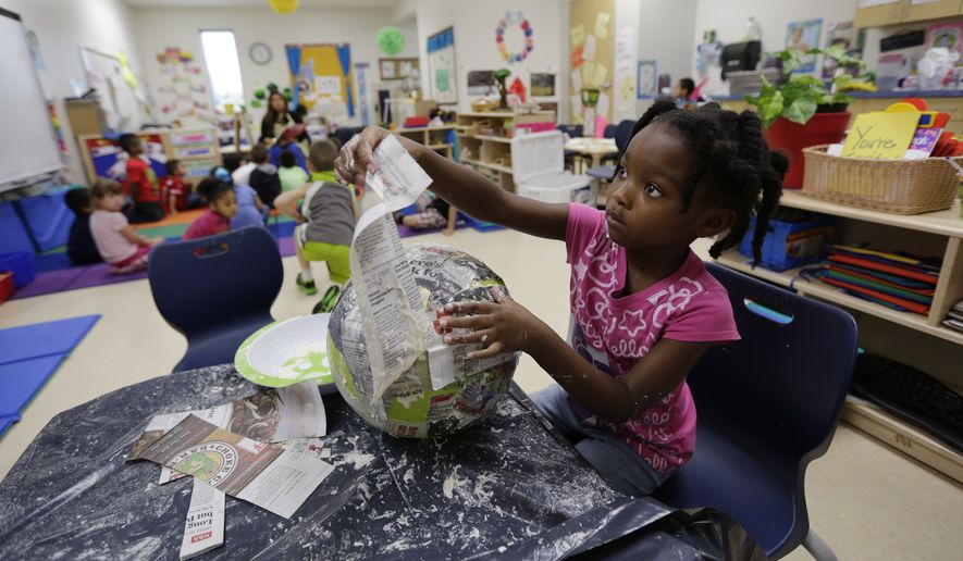 File - In this April 2, 2014 photo, a Pre-K student works papier mache at the South Education Center, in San Antonio. (AP Photo/Eric Gay)