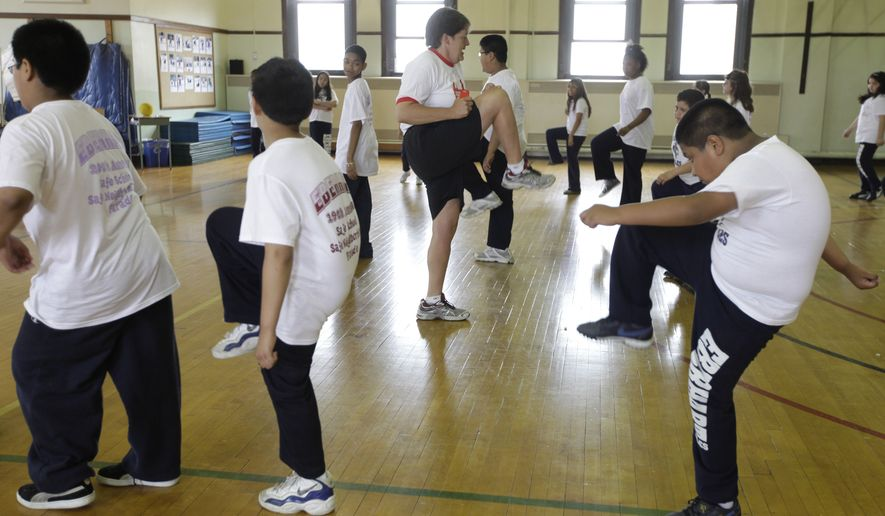 In this May 26, 2009, file photo, Betty Hale, center, instructs a physical education class at Eberhart Elementary School in Chicago. (AP Photo/M. Spencer Green, File)