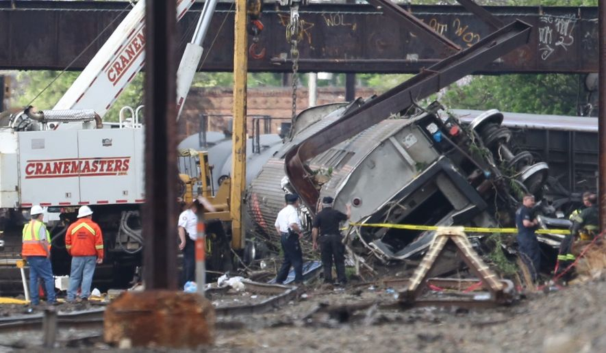 Investigators examine the train derailment site, Wednesday, May 13, 2015, after a fatal Amtrak derailment Tuesday night, in the Port Richmond section of Philadelphia. Federal investigators arrived Wednesday to determine why an Amtrak train jumped the tracks in a wreck that killed at least six people, and injured dozens. (Alejandro A. Alvarez/Philadelphia Inquirer via AP)