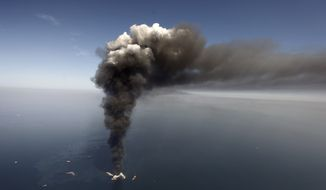Oil can be seen in the Gulf of Mexico, more than 50 miles southeast of Venice on Louisiana's tip, as a large plume of smoke rises from fires on BP's Deepwater Horizon offshore oil rig in this April 2010 file photo. (AP Photo/Gerald Herbert, File)