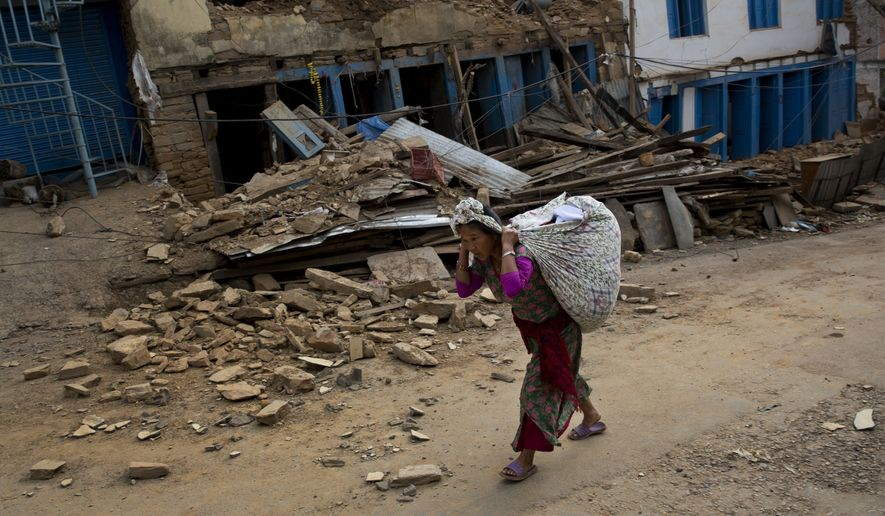 A Nepalese woman carrying belongings walks past a damaged house in Chautara, Nepal, Wednesday, May 13, 2015. The condition of many of the buildings damaged in the April 25 earthquake, got worse after the magnitude-7.3 quake Tuesday. (AP Photo/Bernat Amangue)