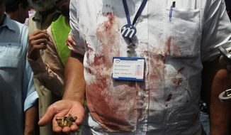 A Pakistani security official displays cartridges he collected from the scene of an attack on a bus, in Karachi, Pakistan, Wednesday, May 13, 2015. Gunmen killed dozens of people on Wednesday aboard a bus in southern Pakistan bound for a Shiite community center, in the latest attack targeting the religious minority, police said. (AP Photo/Fareed Khan)