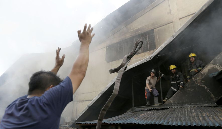 A fireman throws a hose at colleagues at a still-smoldering Kentex rubber slipper factory in Valenzuela city, a northern suburb of Manila, Philippines, Wednesday, May 13, 2015.  (AP Photo/Bullit Marquez)