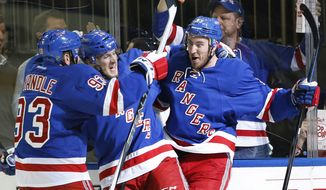 New York Rangers right wing Kevin Hayes (13) celebrates with center J.T. Miller (10) and defenseman Keith Yandle (93) after scoring a goal against the Washington Capitals during the second period of Game 7 of the Eastern Conference semifinals during the NHL hockey Stanley Cup playoffs, Wednesday, May 13, 2015, in New York. (AP Photo/Kathy Willens)