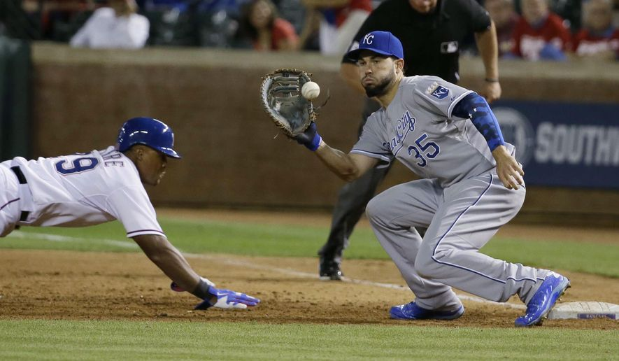 Texas Rangers' Adrian Beltre (29) dives back to first as Kansas City Royals first baseman Eric Hosmer (35) waits for the throw during the ninth inning of a baseball game in Arlington, Texas, Tuesday, May 12, 2015. Beltre was called out on the play after review. The Royals won 7-6 in 10 innings. (AP Photo/LM Otero)