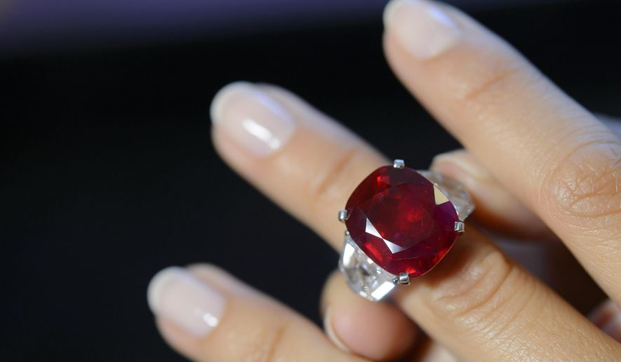 FILE - This May 6, 2015 file photo shows a Sotheby's employee wearing a ruby and diamond ring by Cartier, with a Burmese ruby weighing 25.59 carats, during a preview at the Sotheby's auction house in Geneva, Switzerland. The ring sold for $30.3 million at auction, Tuesday, May 12, setting a world auction record for any ruby and for any stone by Cartier, according to Sotheby's. (Martial Trezzini/Keystone via AP, File)
