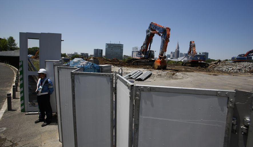 A guard stands by Japan's National Stadium which is dismantled for the renovation Wednesday, May 13, 2015. After a series of delays, demolition of Tokyo's National Stadium has been completed, clearing the way for the building of a new structure that will be the centerpiece of the 2020 Summer Games. (AP Photo/Shizuo Kambayashi)