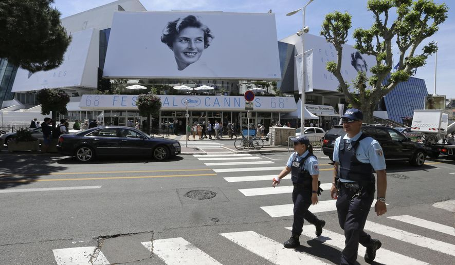 In this photo taken Tuesday, May 12, 2015, municipal police officers patrol outside the Palais des Festivals ahead of the 68th international film festival, Cannes, southern France. France is on heightened terrorist alert after deadly attacks in Paris, and the monied French Riviera offers rich pickings for criminals. That means the world's glitziest film festival, which opens Wednesday, is the focus of an intense security operation to try and keep disaster and drama confined to the screen. (AP Photo/Lionel Cironneau)