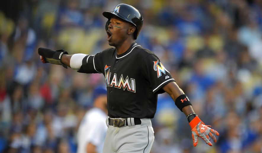Miami Marlins' Dee Gordon celebrates after scoring on a single by Giancarlo Stanton during the seventh inning of a baseball game against the Los Angeles Dodgers, Wednesday, May 13, 2015, in Los Angeles. (AP Photo/Mark J. Terrill)