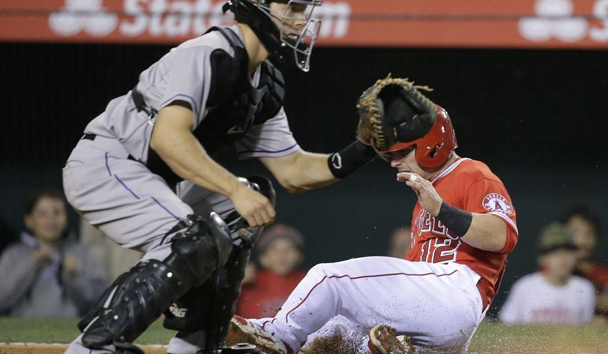 Los Angeles Angels' Johnny Giavotella, right, scores on a single hit by Carlos Perez as Colorado Rockies catcher Nick Hundley waits for the throw during the fourth inning of a baseball game, Tuesday, May 12, 2015, in Anaheim, Calif. (AP Photo/Jae C. Hong)