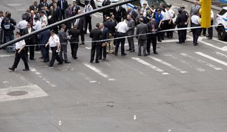 A hammer, bottom center between three white cups, lies in the middle of a Manhattan intersection as police investigators gather, Wednesday, May 13, 2015, after a man apparently wielding the hammer was shot and wounded by police in New York. The shooting took place shortly after 10 a.m. Wednesday blocks from Madison Square Garden and Penn Station in Manhattan. (AP Photo/Mark Lennihan)
