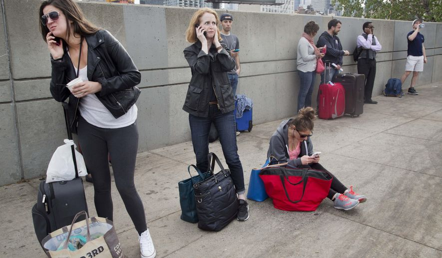 A traveler, center, waits for a bus Wednesday, May 13, 2015, in New York, after the Amtrak train she was scheduled to take to Washington was canceled. The passenger train derailed and overturned in Philadelphia Tuesday, disrupting service on the Northeast Corridor. (AP Photo/Mark Lennihan)