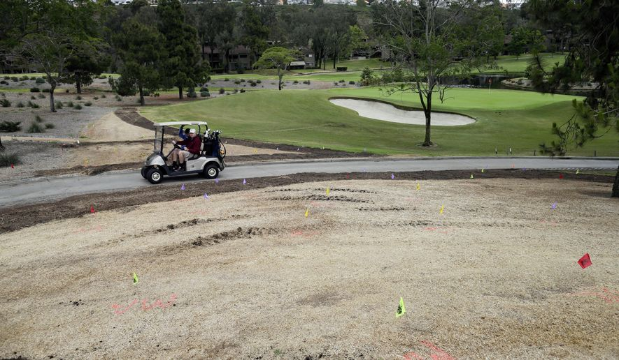 In this April 25, 2015 picture, golfers drive a cart past dry vegetation at the El Niguel Country Club in Laguna Niguel, Calif. California's epic drought is reshaping the course at El Niguel Country Club and dozens of others statewide. Pressed by the fourth year of bone-dry weather and the threat of state-mandated water cuts, some of the poshest courses in California are ceding back to nature some of their manicured green, installing high-tech moisture monitoring systems and letting the turf they don't rip up turn just a little bit brown. (AP Photo/Gregory Bull)