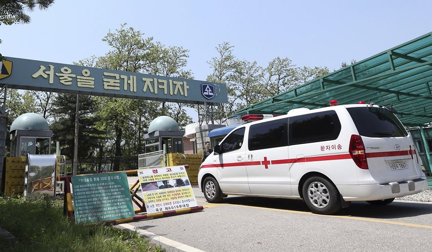 "A military ambulance enters into a reserve forces training camp in Seoul, South Korea Wednesday, May 13, 2015. A South Korean reserve soldier went on a shooting spree Wednesday, killing a fellow reservist and injuring three others before killing himself, army officials said. The letters on the sign read: ""Let's keep Seoul.""  (Shin Joon-hee/Yonhap via AP) KOREA OUT"