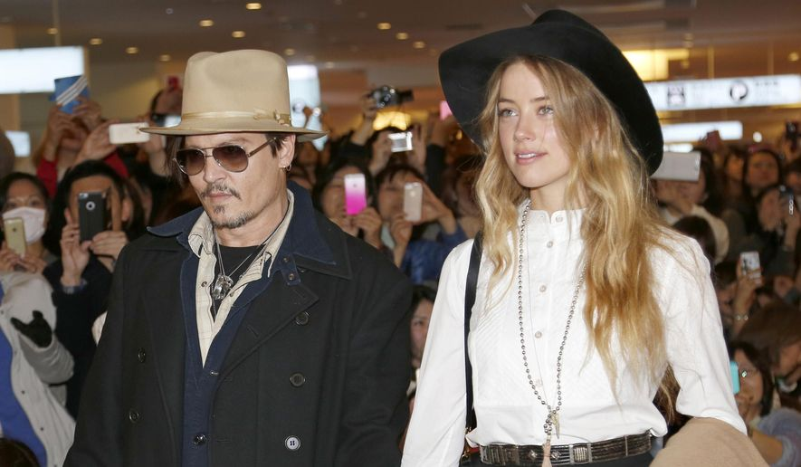 """Actor Johnny Depp and Amber Heard arrive at Haneda International Airport in Tokyo to promote his latest film """"Mortdecai"""" in this Jan. 26, 2015, file photo. (AP Photo/Shizuo Kambayashi, File)"""