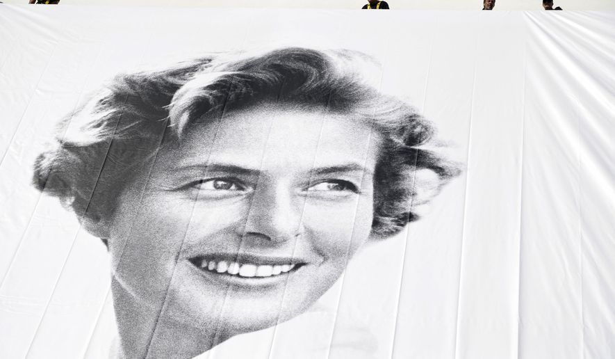 AP10ThingsToSee - Workers hang a banner depicting actress Ingrid Bergman on the Palais during preparations for the 68th international film festival in Cannes, southern France on Monday, May 11, 2015. The festival runs from May 13 to May 24. (AP Photo/Thibault Camus)