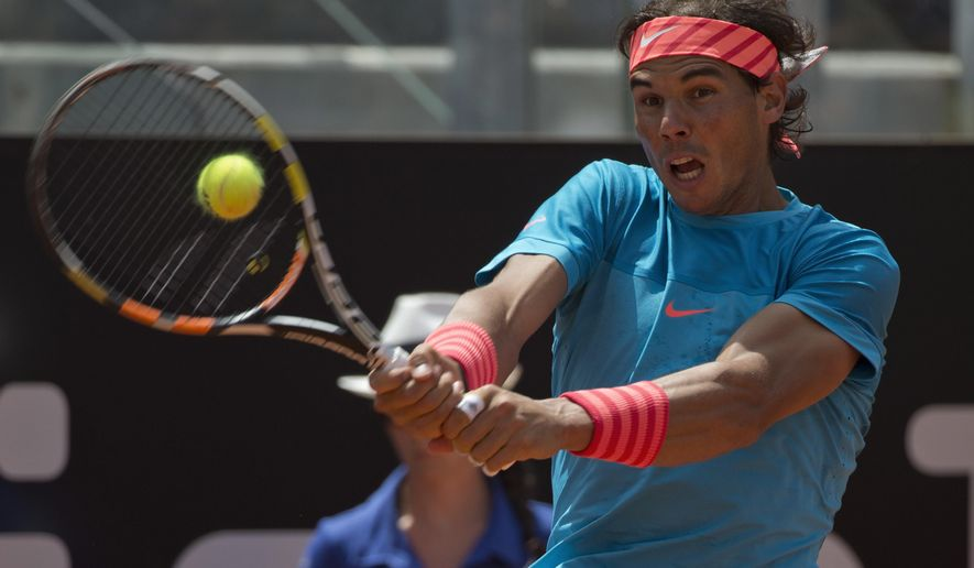 Rafael Nadal, of Spain, returns the ball to John Isner, of the United States, during their match at the Italian Open tennis tournament, in Rome, Thursday, May 14, 2015. (AP Photo/Andrew Medichini)