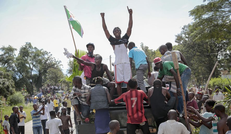 Demonstrators climb aboard a military truck as they celebrate what they perceive to be an attempted military coup d'etat, with army soldiers riding in an armored vehicle in the capital Bujumbura, Burundi Wednesday, May 13, 2015.  Police vanished from the streets of Burundi's capital Wednesday as thousands of people celebrated a rumored coup attempt against President Pierre Nkurunziza. (AP Photo/Berthier Mugiraneza)