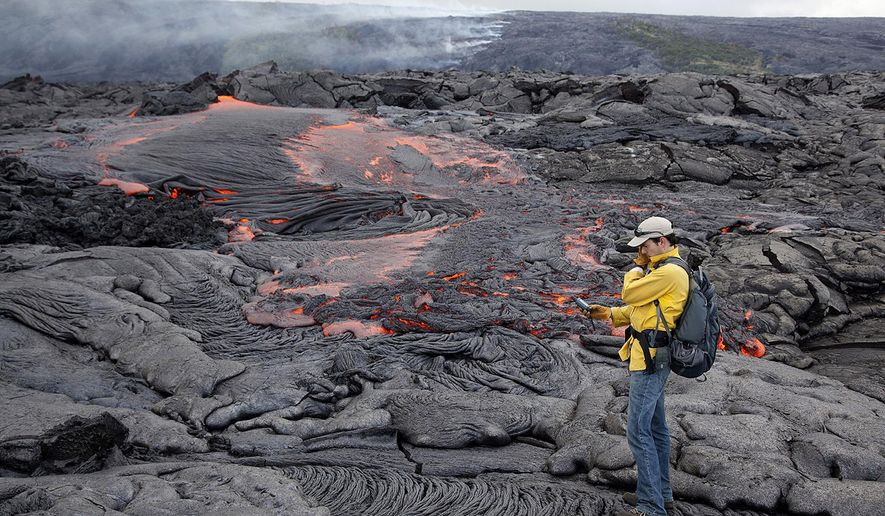 ADVANCE FOR RELEASE SATURDAY, MAY 16, 2015, AT 2:01 A.M. AKDT AND THEREAFTER - This 2012 photo released by the U.S. Geological Survey Hawaiian Volcano Observatory shows Matt Patrick, a research geologist at USGS Hawaiian Volcano Observatory, mapping an active lava flow in Hawaii. For some, getting up-close-and-personal with a swollen, boiling lake of lava might sound terrifying, even nightmarish, but for Patrick, it's a dream come true. (U.S. Geological Survey via AP)