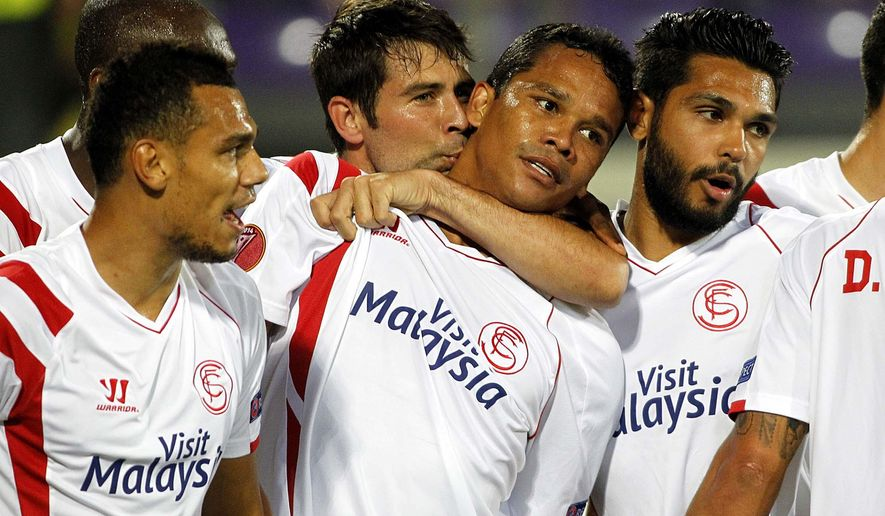 Sevilla's  Carlos Bacca, center, celebrates with teammates after scoring during an  Europa League semifinal, return match, between Fiorentina and Seville, at the Artemio Franchi stadium in Florence, Italy, Thursday, May 14, 2015.  (AP Photo/Fabrizio Giovannozzi)