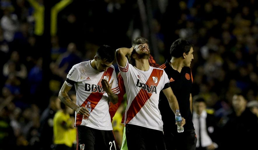Leonardo Ponzio, right, Leonel Vangioni of Argentina's River Plate grimace in pain after pepper spray was thrown at them from the stands before the start of the second half of their Copa Libertadores soccer match against Boca Juniors in Buenos Aires, Argentina, Thursday, May 14, 2015. Conmebol authorities and referee Dario Herrera cancelled the game due to the incident. (AP Photo/Natacha Pisarenko)