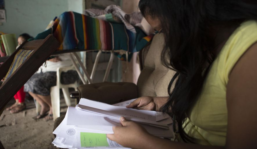 FILE - In this Dec. 23, 2014 file photo, a woman who spoke on the condition of anonymity in fear retribution by officials and drug traffickers, looks through court documents at her home in Arcelia, Mexico, during her first interview since being tortured and falsely imprisoned for five months on weapons possession charges. The Mexican government said Thursday, May 14, 2015 it will give at least 50 million pesos ($3.3. million) to the relatives of criminal suspects slain in 2014 by soldiers and survivors of the shootings, after a rights investigation found 12 to 15 of the 22 suspects were killed by army troops after surrendering. The investigation found the victims included three women who survived the attack and were tortured or pressured to support the army's version that all 22 suspects were killed in a shootout. (AP Photo/Christian Palma, File)