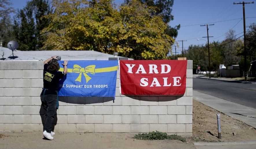 Volunteer Rose Sliepka removes a flag after a yard sale held to benefit Jerral Hancock, a 27-year-old Iraq war veteran who lost his left arm and was paralyzed from the waist down in a bomb explosion in Iraq, on Saturday, Oct. 26, 2013, in Lancaster, Calif. When the seniors in Jamie Goodreau's high school history class learned Hancock was once stuck in his modest mobile home for months when his handicapped-accessible van broke down, they decided to build him a new house from the ground up.  It would be their end-of-the-year project to honor veterans, something Goodreau's classes have chosen to do every year for the past 15 years. (AP Photo/Jae C. Hong)