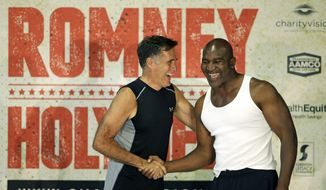 Former Republican presidential candidate Mitt Romney, left, and five-time heavyweight boxing champion Evander Holyfield shake hands after an official weigh-in Thursday, May 14, 2015, in Holladay, Utah. Romney and Holyfield are set to square off at a charity fight on Friday, May 15, in Salt Lake City. (AP Photo/Rick Bowmer)