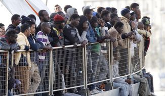 In this May 6, 2015, file photo, migrants wait to disembark from the Iceland Coast Guard vessel Tyr, at the Messina harbor, Sicily, southern Italy. (AP Photo/Antonio Calanni, File)